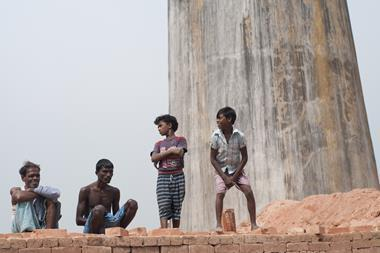 Workers and their family members standing on stacks of bricks in a brick factory where they work and stay under tough and unhealthy conditions