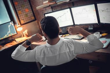 Rear view of stock trader stretching hands at workplace