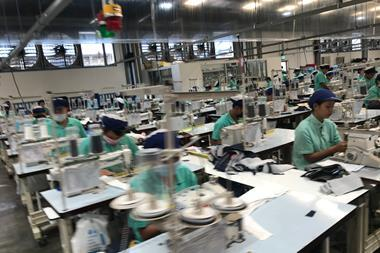 Worker producing clothes in garment factory